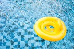Sväva den gula cirkeln på swimpool för blått vatten med vågreflectin arkivbild