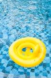 Sväva den gula cirkeln på swimpool för blått vatten med vågreflectin royaltyfria bilder