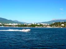 Sväva den vita motorbåten på bakgrund av staden på sjösida med det stora berget Royaltyfria Bilder