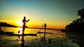 Sväva folk på solnedgången på vattnet royaltyfri bild