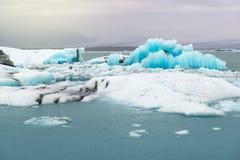 Sväva isberg och sikt till glaciären, islagun Jokulsarlon, Island Arkivbilder