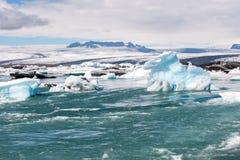 Sväva isberg och sikt till glaciären, islagun Jokulsarlon, Island Royaltyfria Bilder