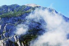 Sväva moln och dimma överst av berget Arkivfoton