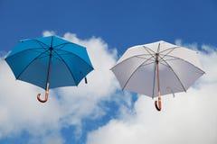 Sväva paraplyer i blått och vit Fotografering för Bildbyråer