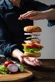 Svävninghamburgare mellan händerna på en mörk bakgrund Flyga ingredienser hamburgare eller ostburgare ovanför plattan Utrymme f?r royaltyfria foton
