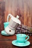 Svävningkaffe Kaffebryggarekaffe med det stängda locket Kaffe för blå kaffebryggare för pastell hällande in i en kopp Torr lavend royaltyfri foto
