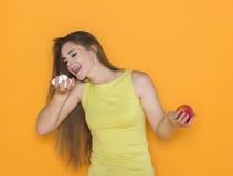 Svårt val mellan sötsaker och sund mat Fotografering för Bildbyråer