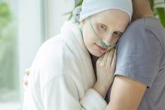 Svag kvinna med cancer som kramar hennes make under kemoterapi arkivfoton