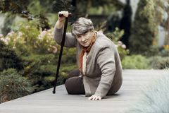 Svag kvinna med väntande på hjälp för gå pinne efter breathlessnessattack arkivbilder