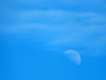 Svaga måne och moln i en blå himmel arkivbild