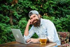 Svago brutale dell'uomo con birra ed il gioco di sport I pantaloni a vita bassa barbuti del tifoso fanno per scommettere il compu fotografia stock