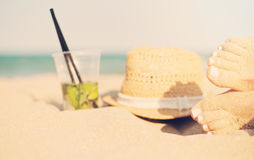 Svago di estate - bella dei piedi delle donne, delle gambe femminili sulla spiaggia sabbiosa con il cappello e del cocktail  Fotografie Stock Libere da Diritti