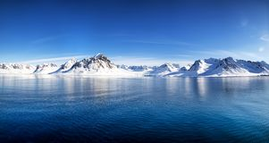 Svalbard mountains and fiords panorama. Blue sky, blue and snowy mountains in the beautiful fjords of Svalbard, a Norwegian archipelago between mainland Norway royalty free stock images