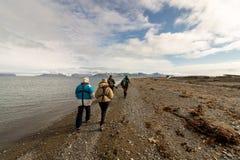 Svalbard Norge, Augusti 3, 2017: Grupp av turister som går på stranden på Prins Karls Forland på Svalbard som söker efter Arkivbilder