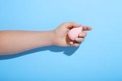 Svamp för makeup för hand för kvinna` s hållande på blå bakgrund Arkivbilder