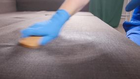 svampar för flytande för cleaningbegreppsdishwashing Arbetaren för den unga mannen gör ren soffan i rummet eller kontoret lager videofilmer