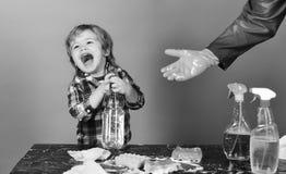 svampar för flytande för cleaningbegreppsdishwashing Unge med att skratta framsidahållsprej på tabellen Royaltyfri Fotografi