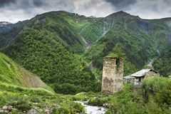 Svan ancient tower in mountain village in Svaneti region of Georgia. Mountains covered green grass. Georgian nature. Royalty Free Stock Photo