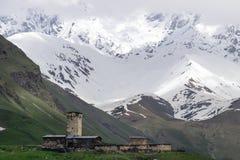 Svan hus och watchtowerUshguli by mot bakgrunden av snö-korkade berg Shkhara Royaltyfria Foton
