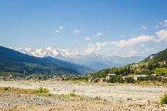Svan står högt i den Mestia byn i Kaukasus berg Royaltyfri Bild