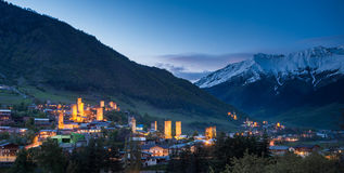 Svan towers with illumination in Mestia at sunrise, Svaneti, Georgia. View of the Svanetian towers with night illumination in Mestia village against snowy Stock Image