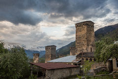 Svan towers in Mestia at sunrise, Svaneti, Georgia. View of the Svanetian towers in Mestia village against snowy mountains. Upper Svaneti, Georgia Royalty Free Stock Photography