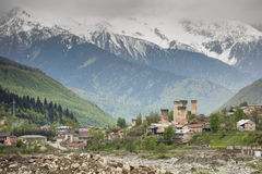 Svan towers in Mestia at sunrise, Svaneti, Georgia. View of the Svanetian towers in Mestia village against snowy mountains. Upper Svaneti, Georgia Royalty Free Stock Photo