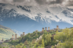 Svan towers in Mestia at sunrise, Svaneti, Georgia. View of the Svanetian towers in Mestia village against snowy mountains. Upper Svaneti, Georgia Royalty Free Stock Image