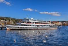 Svanar och ms Linth på en pir på sjön Zurich Arkivfoton