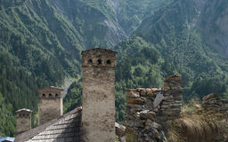 Svaneti towers. Traditional Svaneti stone towers against green mountains background stock photography