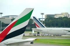 Svansar av Air France Boeing 777-300ER och emirater Boeing 777-300ER på den Changi flygplatsen Arkivbild