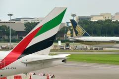 Svansar av Singapore Airlines Boeing 777-200ER och emirater Boeing 777-300ER på den Changi flygplatsen Arkivfoto
