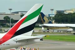 Svansar av Singapore Airlines Boeing 777-200 och emirater Boeing 777-300ER Arkivfoton
