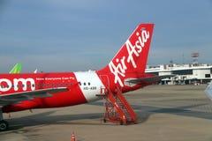 Svansen av nivån av thailändska Airasia, flygbussen A320 parkeras på parkeringsplatsen och mot passagerarelogitrappuppgången arkivfoton