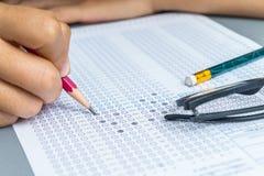 Svar för student för selektiv fokus fyllnads- ut till ett prov med en blyertspenna arkivfoto