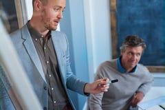Svarande frågor för ung affärsman under en presentation till coworkers Fotografering för Bildbyråer