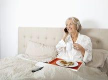 Svarande mobiltelefon för lycklig hög kvinna, medan ha frukosten i säng Arkivbild
