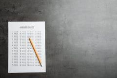 Svarsark och blyertspenna på grå bakgrund, bästa sikt arkivfoton