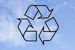 Svart återanvänder symbolen på bakgrunden av himmel Arkivbild