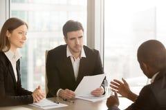 Svart affärsman som övertygar partners för att underteckna dokumentet, negotiat arkivfoton