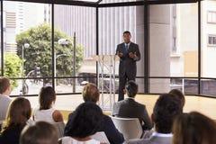 Svart affärsman som framlägger seminariet som gör en gest till åhörare arkivfoto