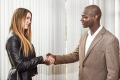 Svart affärsman som skakar händer med en blond caucasian kvinna Royaltyfria Foton