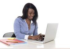 Svart afrikansk amerikanetnicitetkvinna som arbetar på datorbärbara datorn på att le för kontorsskrivbord som är lyckligt arkivfoton