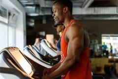 Svart afrikansk amerikankroppsbyggareutbildning på trampkvarnen i idrottshall Royaltyfria Bilder