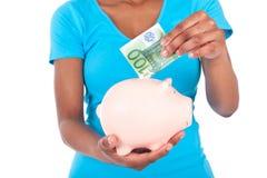 Svart afrikansk amerikankvinna som sätter in en euroräkning inom en smil Royaltyfri Fotografi