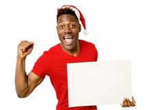 Svart afro amerikansk man i juljultomtenhatt som ler lyckligt utrymme för kopia för visningmellanrumsaffischtavla Royaltyfria Bilder