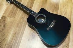 Svart akustisk gitarr på trägolvet Fotografering för Bildbyråer