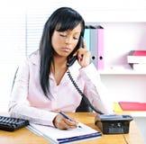 svart allvarlig affärskvinnaskrivbordtelefon Arkivfoto