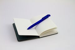 Svart anteckningsbok med blåttpennan Arkivbild