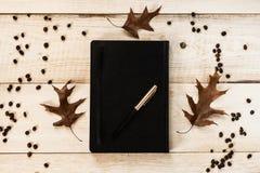 Svart anteckningsbok med en penna, tre stupade sidor och kaffebönor arkivbilder